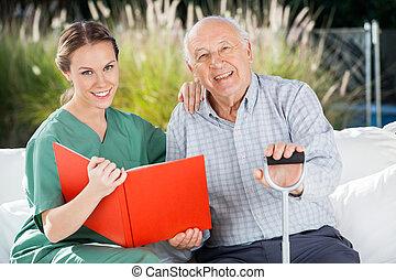 sourire, livre, femme, infirmière, homme aîné