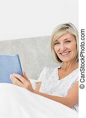 sourire, mûr femme, utilisation, tablette numérique, dans lit