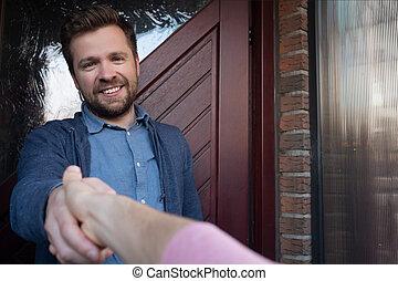 sourire, secousse, ouverture, ami, jeune homme, accueillir, lui, porte, sien, main.