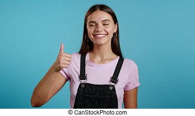 sourires, jeune, positif, signe, corps, appareil-photo., haut, arrière-plan., success., mignon, pouce, girl, language., femme, sur, projection, bleu, winner.