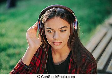 sourires, musique, par, girl, écouteurs, rhythm., jeunesse, concept, jeune, park., chemise, écoute, étudiant, moderne, plaid, danse, liberté, adolescent, rouges, vie