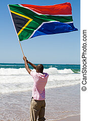south africa - a man waving the south african flag on a...