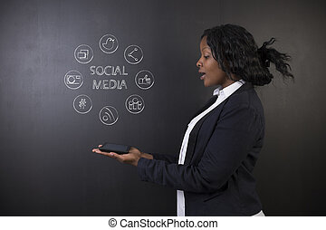 South African or African American woman teacher or student hholding tablet social media