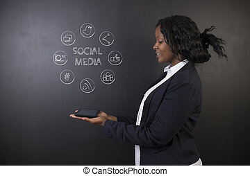 South African or African American woman teacher or student holding tablet social media