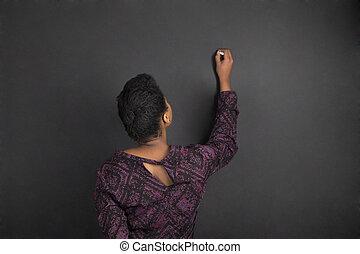 African American woman teacher writing on chalk black board background