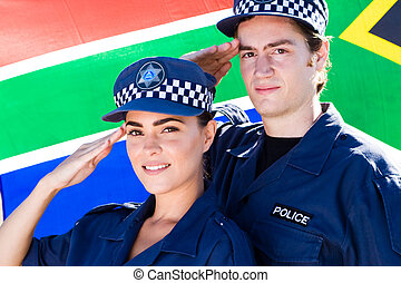 south african police officers salutingin front of south african flag