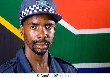 south african policeman - a policeman standing in front of...