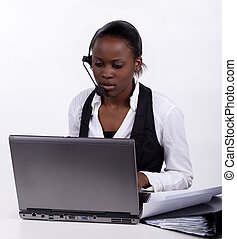 South African woman with telephone headset doing administration.