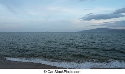 Panning coastline scene with islands on the horizon and cloudy skies looking out over the south china sea in vietnam, high definition movie clip stock footage. Panoramic.