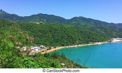 Turquoise South China Sea in Vung Ro Bay dotted with small wooden fishing boats in central Vietnam with a mountainous tropical backdrop.