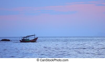 Fisherman in a small wooden fishing boat navigating across the south china sea, under tropical sunset skies high definition stock footage clip.
