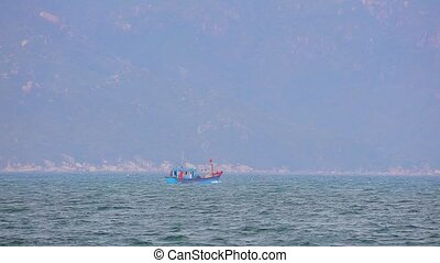 South China Sea and small wooden fishing boats in central Vietnam with a mountainous backdrop. Tropical asian landscape scene with a turquoise ocean.