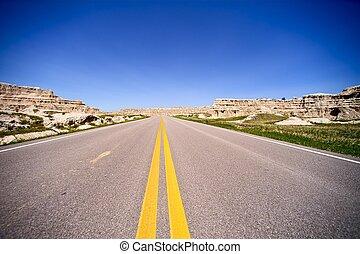 South Dakota Highway, USA. HIghway Through Badlands Landscape. Single Lane Roadway. Transportation Photography Collection.