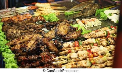 Traditional Asian meat satay street food cooking outdoor at night. South East Asia
