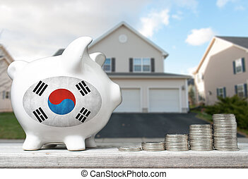 South Korean real estate investment concept with piggy bank, stacks of coins and house in the background