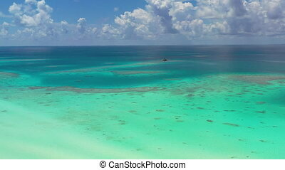 Blue and turquoise sea. South Pacific Ocean aerial view of coral reef blue sky and waves on beach in French Polynesia, Tahiti. Fakarava atoll and famous Blue Lagoon.