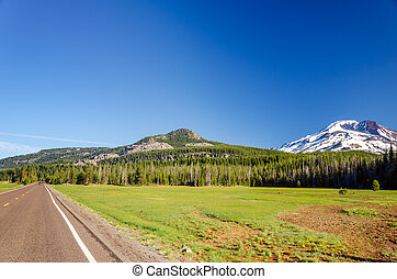 Highway passing next to a forest and South Sister mountain near Bend, Oregon