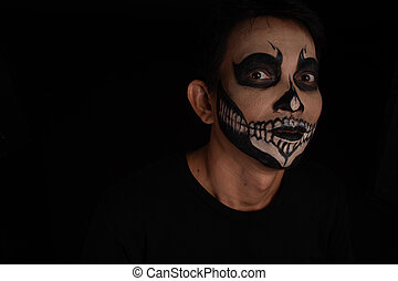 Southeast asian man with skull face makeup on black background, portrait photography