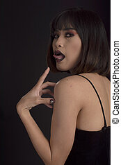 Southeast asian woman with dark tone makeup sticking out her tongue