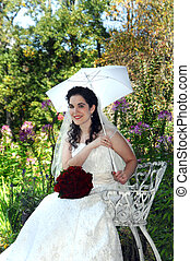 Southern Bell - Bride poses, sitting on white, metal chair....