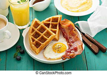 Southern cuisine breakfast with waffles, bacon and egg
