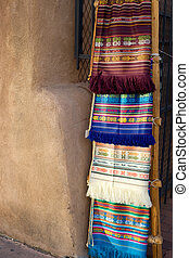Traditional southwestern rugs on display in Santa Fe marketplace
