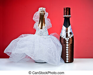 Souvenir bottles for a wedding on a red background. figurines of