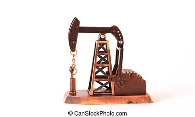Souvenir oil pump spin clockwise about of axis on white background