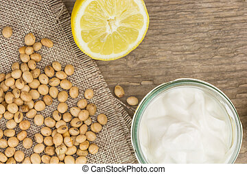 Soy mayonnaise, lemon and soybeans, on wooden background