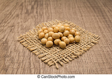 Soybean legume. Grains on square cutout of jute. Wooden table. Selective focus.