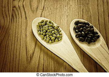 Soybeans and black beans in wooden spoons