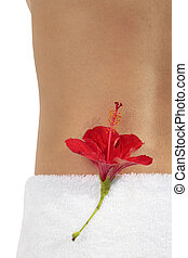 Spa Abstract - Woman at a spa with a red hibiscus flower on...