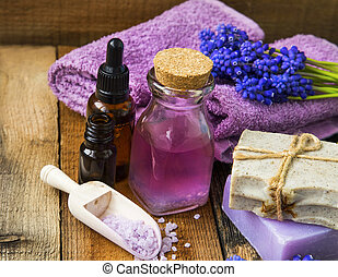 Spa and aromatherapy oil,towels, purple flowers, soap, bath salt on wooden background
