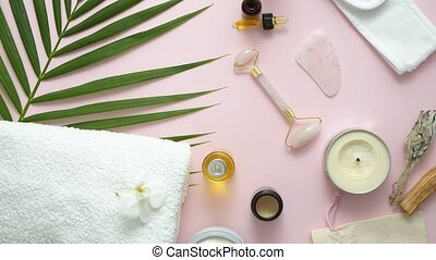 Spa and body care composition. Wellness and beauty treatment. Gua sha massager, natural oils and creams. Flat lay assortment of pink background.