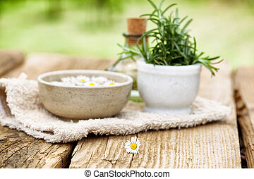 Spa and wellness setting with flowers, floral water and towel. Natural spa setting