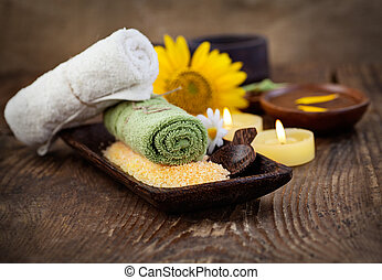Spa and wellness setting with natural bath salt, candles and towel, massager and sunflower.. Brown dayspa nature set with copyspace