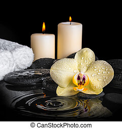 spa background of yellow orchid (phalaenopsis) on zen stones, drops, candles and stacked of towels with ripple reflection water, close up