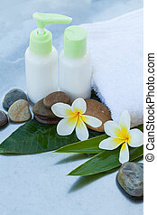 Spa background with green leaves, stones, flowers and cosmetics treatment
