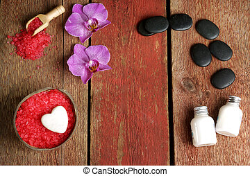 Spa background with orchid, red salt for coconut baths, body lotions and stones for hot massage on a wooden table with copy space for your text