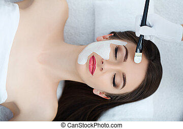 Spa. Beautician applies the mask to the face of beautiful young woman in the spa salon. spa treatments