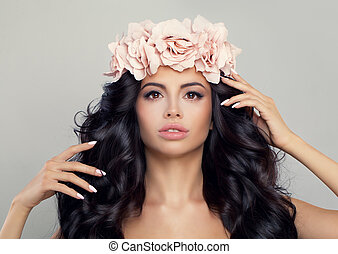 Spa Beauty. Beautiful Woman in Flowers Wreath. Perfect Model with Natural Makeup, Healthy Skin, Curly Hair and Roses Flowers