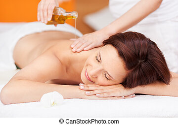 Spa beauty treatment with oil - Beautiful young woman ...