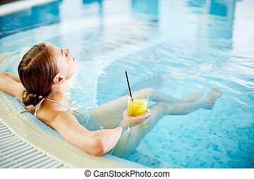 Spa break - Woman enjoying in swimming pool after procedures