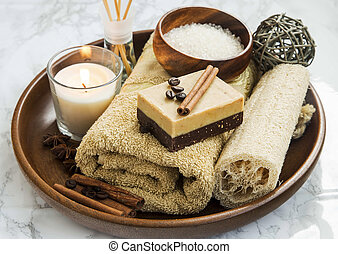 Spa-care products with coffee and cinnamon soap, towel and candle