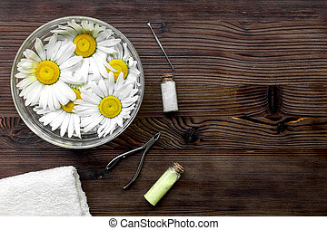 Spa composition on dark wooden desk with chamomile, towel and nippers copyspase top view