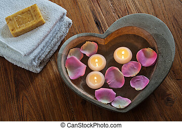 spa composition with stone heart filled with water rose...