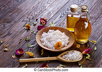 SPA concept: composition of spa treatment with natural sea salt, aromatic oil and flowers on wooden background