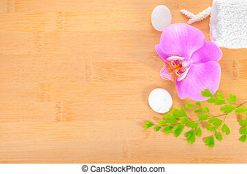 spa concept, lilac orchid and white towels on the bamboo background
