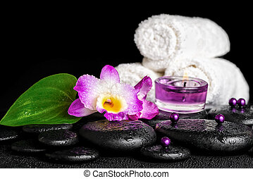 spa concept of orchid flower, zen basalt stones with drops, purple candles, beads and white towels, closeup
