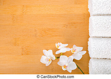 spa concept, white orchid and white towels on the bamboo background